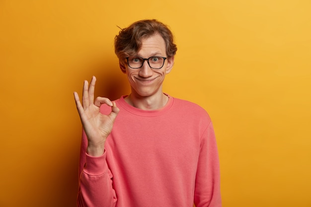 Je suis d'accord avec votre suggestion. sourire bel homme sourit agréablement, fait signe d'accord, exprime son approbation, porte des lunettes et un pull rose, a tout sous contrôle, isolé sur un mur jaune