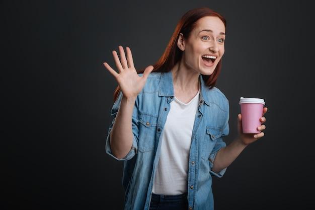 Je suis là. adorable fille excitée lumineuse ayant une tasse de café et en courant dans son amie tout en agitant sa main pour saluer