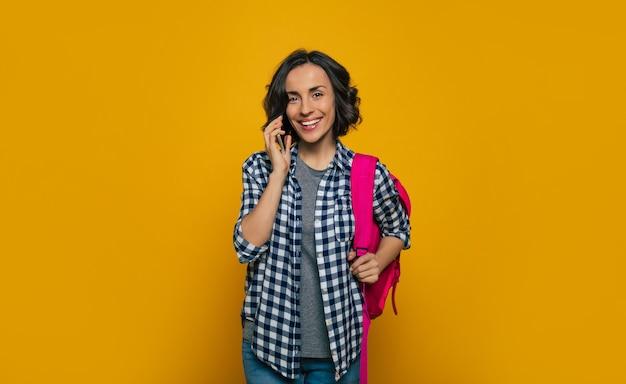 Je suis au téléphone! une belle jeune étudiante, habillée avec désinvolture, avec son joli sac à dos rose sur une épaule, tenant son smartphone dans sa main près de l'oreille, parlant sur le smartphone.