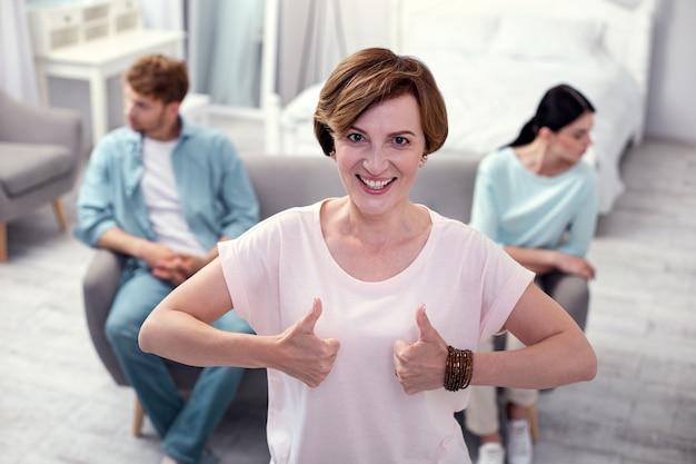 Je suis content. belle femme positive montrant des signes ok tout en étant de bonne humeur