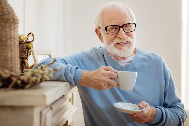 Je suis détendue. heureux retraité tenant la tasse et gardant le sourire sur son visage