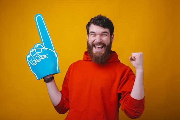 Je suis fan numéro un. photo d'un homme barbu portant un gant d'éventail en mousse bleue sur un espace jaune.
