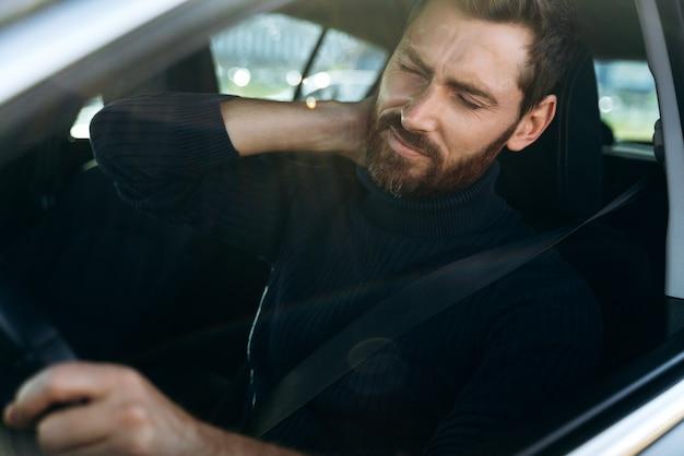 Je suis fatigué. vue depuis la rue du jeune homme se frottant le cou douloureux, tout en ayant l'air fatigué de conduire. conducteur masculin ayant des douleurs au cou, assis dans sa voiture