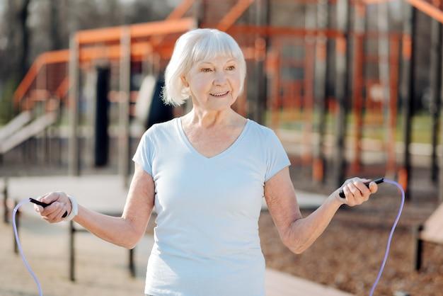 Je suis en forme. corde à sauter femme mince ravie tout en exerçant en plein air