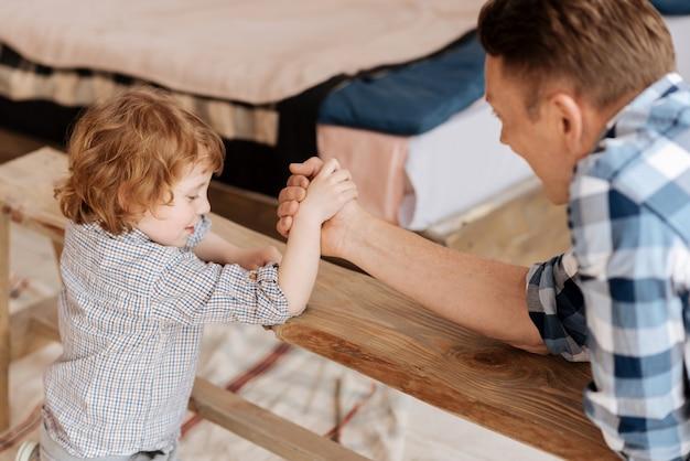 Je suis fort. fils heureux positif assis en position semi-penchés les coudes sur le banc tout en tenant la main avec le père