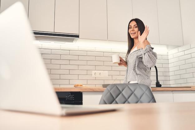 Je suis là. heureuse jeune femme gardant le sourire sur son visage tout en regardant son ordinateur
