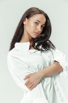 Je suis jeune et jolie. portrait de la belle fille aux cheveux noirs sur studio gris