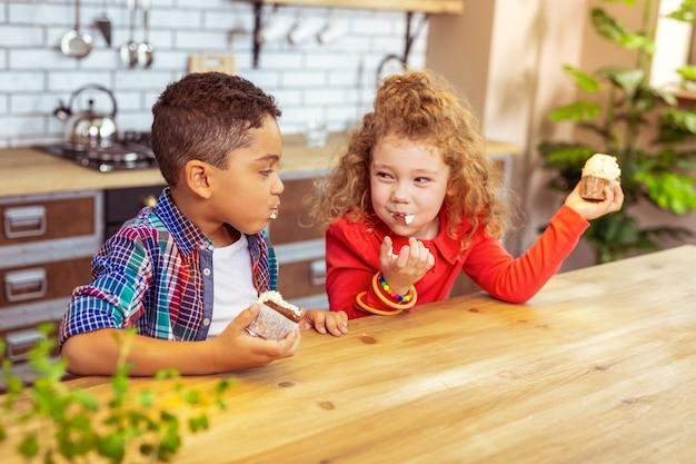 Je suis plus rapide. belle fille tenant un gâteau dans la main gauche et regardant son amie