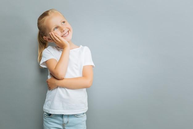 Je suis satisfait. enfant ravi positif en gardant le sourire sur son visage et en se penchant la tête sur la main droite en se tenant debout sur fond gris