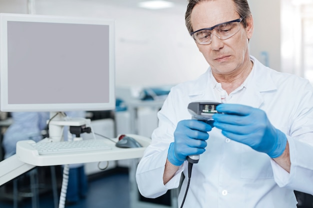 Je suis sérieux. homme réfléchi portant des lunettes de protection et en appuyant sur les lèvres tout en faisant une analyse de sang
