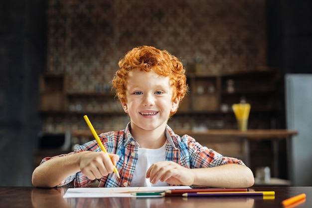 Je suis tellement heureux en ce moment. portrait d'un garçon rousse regardant dans la caméra avec un sourire joyeux sur son visage assis à une table et dessin avec des crayons colorés.