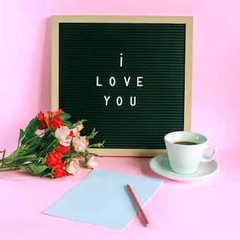 Je t'aime à bord avec tasse de café, roses et crayon sur papier blanc isolé sur fond rose
