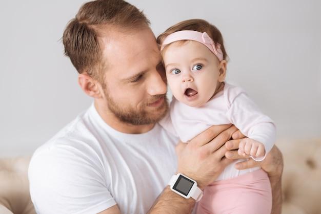 Je t'aime. charmant jeune père positif assis sur le canapé à la maison et étreignant sa petite fille tout en exprimant la positivité et l'amour
