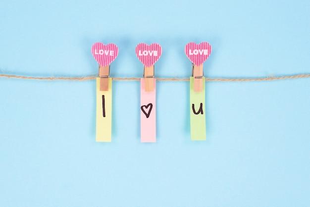 Je t'aime concept. photo en gros plan de trois petites pinces à linge en bois tenant des autocollants avec texte isolé fond de couleur pastel