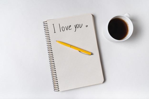Je t'aime écrit sur un cahier sur blanc. café du matin et message pour les proches