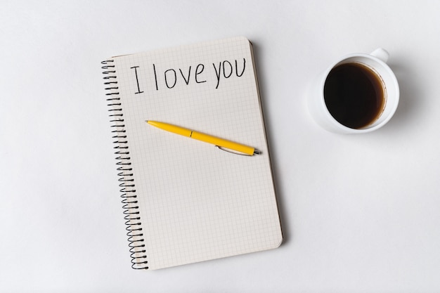 Je t'aime, écrit sur un cahier. café du matin et message pour aimé.