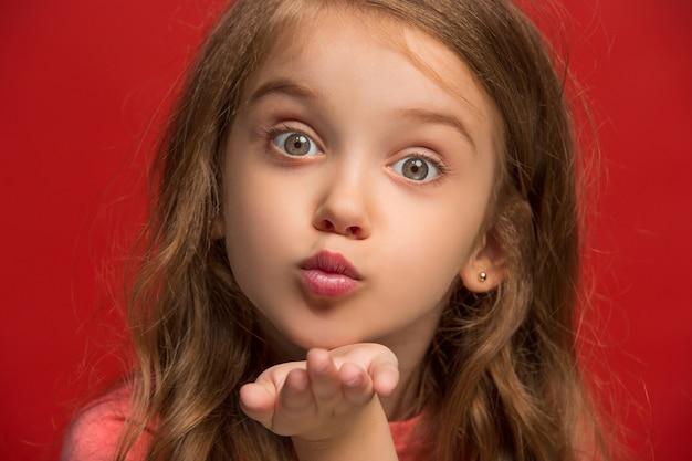 Je t'aime. heureuse adolescente debout, souriant isolé sur rouge à la mode. beau portrait féminin.