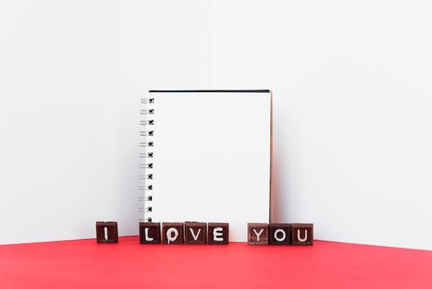 Je t'aime inscription sur des bonbons au chocolat avec le bloc-notes