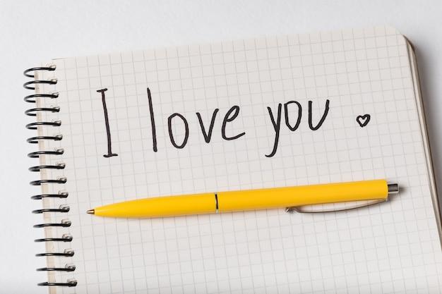 Je t'aime, inscription dans le cahier. stylo sur le bloc-notes.