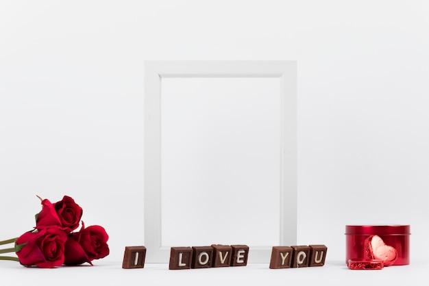 Je t'aime inscription sur des morceaux de chocolat près du cadre photo, des fleurs et une boîte