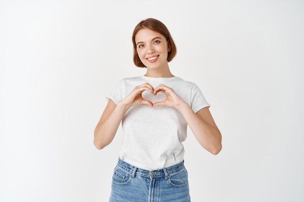 Je t'aime. jolie fille naturelle aux cheveux courts, montrant le signe du coeur et souriant, debout sur un mur blanc