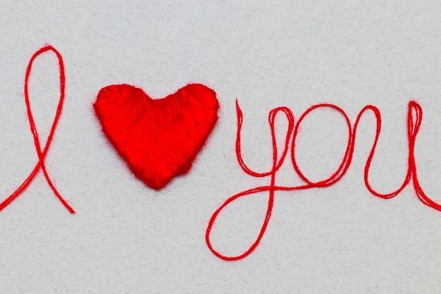 Je t'aime mots et symbole de coeur en fil rouge sur fond blanc pour la saint-valentin