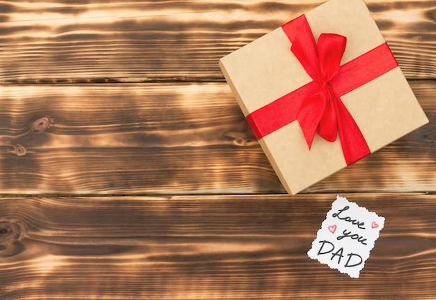 Je t'aime papa carte et coffret cadeau avec arc rouge sur fond de planches de bois avec espace de copie