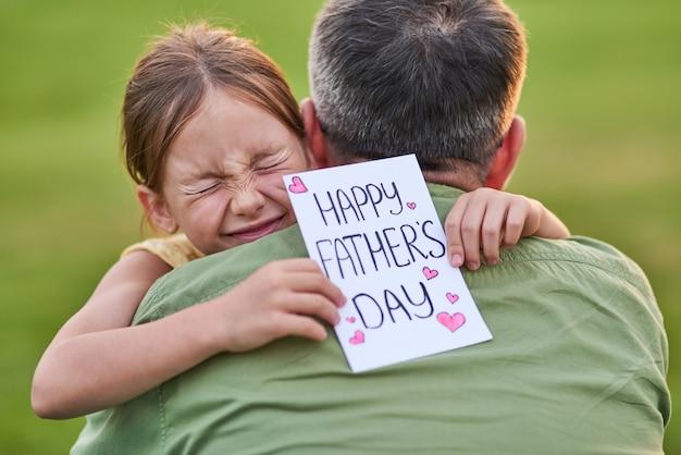 Je t'aime papa mignonne petite fille qui a l'air émotive tout en saluant son papa et en lui donnant à la main