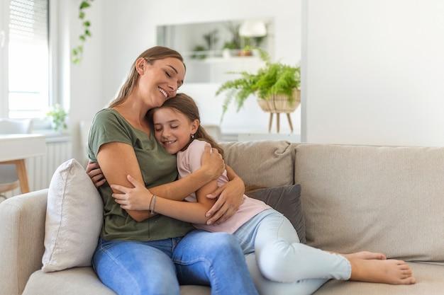 Je t'aime tellement. portrait d'une jeune mère heureuse portant une jolie petite fille souriante dans le salon, une fille d'âge scolaire affectueuse embrassant une nounou ou une mère adoptive bien-aimée