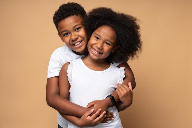 Je t'aime. vue portrait à la taille du charmant garçon multiracial embrassant avec tendresse sa sœur bouclée et regardant la caméra. notion de relations familiales