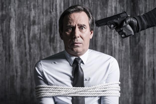 Je t'en prie, non! homme d'affaires ligoté attrapé par un criminel visant sa tête avec une arme à feu