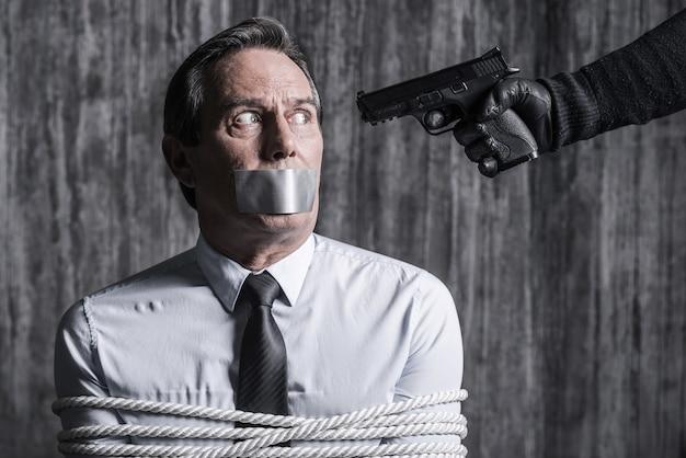 Je t'en prie, non. homme d'affaires ligoté avec du ruban adhésif sur la bouche, assis devant le mur sale pendant que quelqu'un vise sa tête