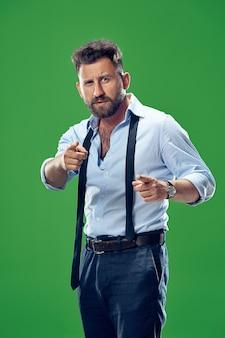 Je te choisis et commande. homme d'affaires envahissant, vous voulez, vous voulez, portrait agrandi de demi-longueur sur fond de studio vert.