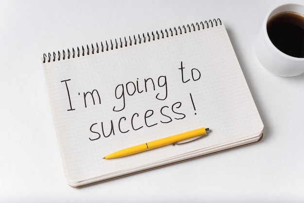 Je vais à l'avis de réussite. stylo pour ordinateur portable et tasse de café sur blanc.