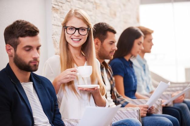 Je vais avoir ce travail ! groupe de jeunes en tenue décontractée élégante assis dans une rangée sur les chaises et tenant des papiers pendant que la belle femme boit du café et sourit