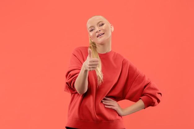 Je vais bien. femme d'affaires heureuse, signez ok, souriant, isolé sur fond de studio de corail à la mode. beau portrait de femme en demi-longueur. femme émotionnelle. émotions humaines, concept d'expression faciale