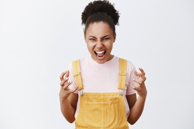 Je vais vous étouffer à mains nues. portrait de femme afro-américaine émotive en colère et énervée en salopette jaune à la mode, faisant des gestes avec les paumes de la haine, criant de colère sur un mur gris