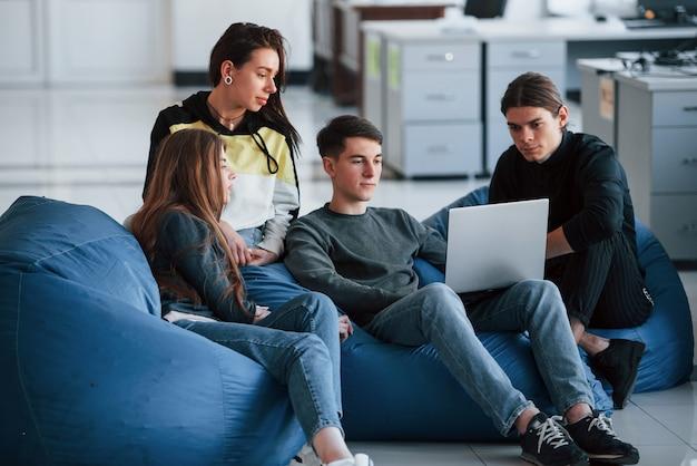 Je veux entendre vos opinions à ce sujet. groupe de jeunes en vêtements décontractés travaillant dans le bureau moderne