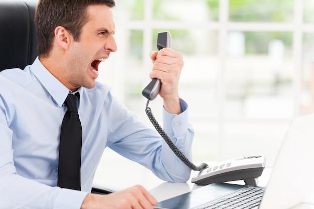 Je veux ce rapport maintenant ! jeune homme furieux en chemise et cravate criant au téléphone alors qu'il était assis sur son lieu de travail