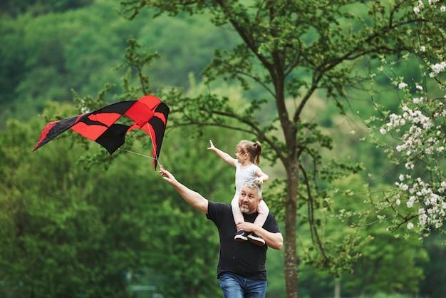 Je veux le tenir. courir avec cerf-volant rouge. enfant assis sur les épaules de l'homme. s'amuser