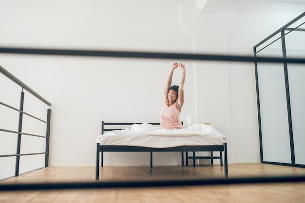 Je viens de me réveiller. une jolie jeune femme assise sur le lit en lingerie rose et s'étirant