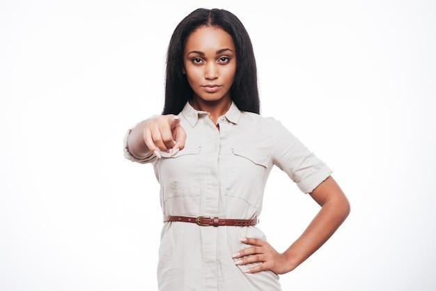 Je vous ai choisis! confiant jeune femme africaine vous pointant en se tenant debout sur fond blanc