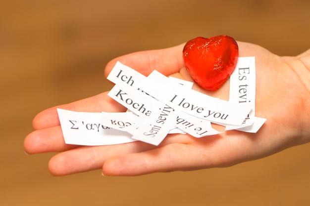 Je vous aime. les mots, imprimés sur des papiers en différentes langues sur votre paume