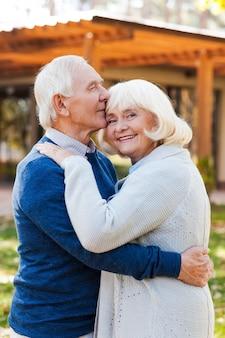 Je vous aimerai pour toujours! joyeux couple de personnes âgées se liant les uns aux autres et souriant tout en se tenant à l'extérieur et devant leur maison