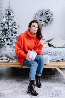 Je vous souhaite un joyeux noël! fille avec un cadeau de noël à la recherche de côté. sentiment heureux au nouvel an. fête de noël!