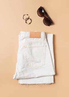 Jean blanc et denim fashion à plat avec accessoires sur beige