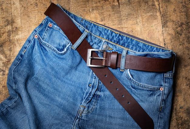 Jean bleu avec ceinture sur la texture en bois ancien .background