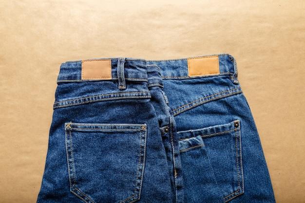 Jean bleu classique. pantalons décontractés portant des jeans bleus avec des étiquettes en cuir vierge marron sur fond beige artisanal. vue de dessus.