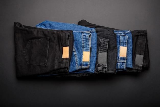 Jean bleu denim et jean noir empilés en tas sur fond noir vue de dessus. les pantalons en jean denim portent des plis en pile.