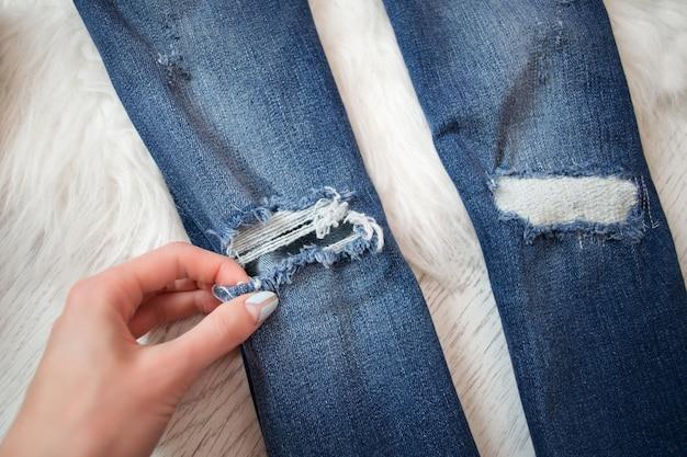 Jean déchiré bleu dans une main féminine. détail. à la mode